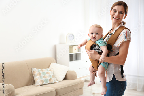 Woman with her son in baby carrier at home. Space for text Canvas Print