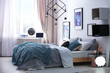 Stylish room interior with comfortable bed and decor