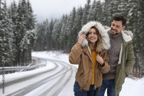 Couple walking near snowy forest, space for text. Winter vacation