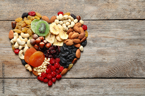 Heart made of different dried fruits and nuts on wooden background, top view. Space for text