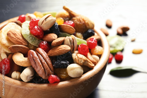 Bowl with different dried fruits and nuts on table, closeup