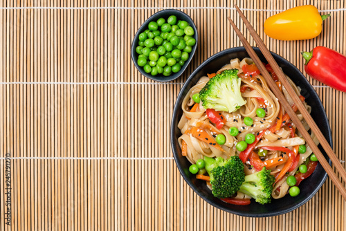 Asian noodle stir fry with vegetables and beans in bowl on bamboo background Canvas Print
