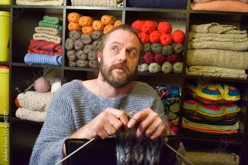Fotografia  Bearded man sits and knits