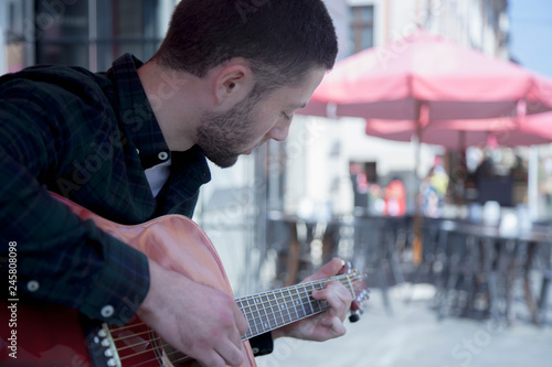 Caucasian man playing the guitar outdoors on summer day in old european city. Rest, tourism, music concept. - 245808098