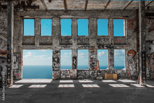 Photo sur Aluminium Les vieux bâtiments abandonnés Abandoned factory ruin / warehouse loft with windows and ocean and blue sky background