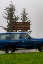 Blurry Truck Drives In Front Of Asheville Or Smoky Mountains Sign