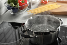 Pot With Boiling Water On Electric Stove In Kitchen, Space For Text