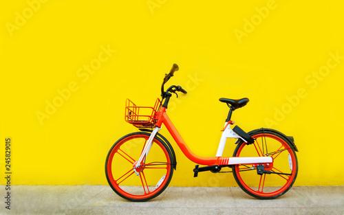 Türaufkleber Fahrrad Bright orange bike stands near the yellow wall.