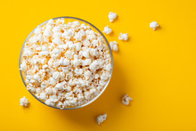 Glass Bowl With Salted Popcorn On Yellow Background. Top View With Copy Space. Flat Lay