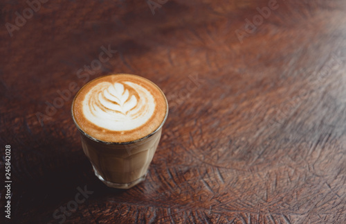 Fotografie, Obraz  Close up coffee cup with latte art on grunge wood table at cafe.