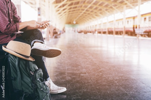 Obraz portrait the tourist young man traveler with backpack sit waiting train station and public car look at the he hand use the phone to check the schedule to leave travel at the station.Travel concept. - fototapety do salonu