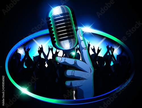 Fotografía Hand holding Retro Mic/ Microphone in front of huge silhouetted crowd waving arms & cheering signifying a concert, pub, karaoke or talent show