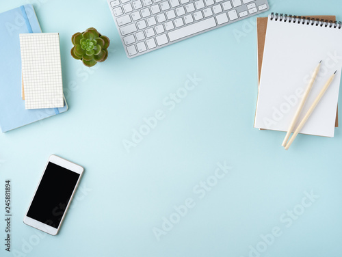 Top view of modern blue office desktop with blank notepad, computer, smartphone. Mock up, empty space Wall mural