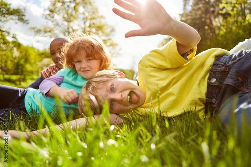 Photo sur Aluminium Attraction parc Kinder spielen und albern herum auf einer Wiese