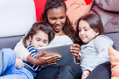 Fototapeta Multi ethnic siblings sitting on sofa watching videos on digital tablet obraz