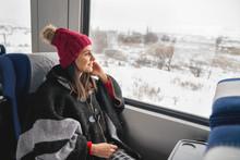 Young Woman Traveler Sitting In Train, Looking Through Big Window.