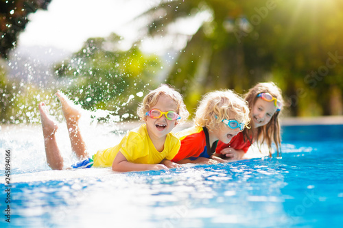 Kids in swimming pool. Children swim. Family fun.