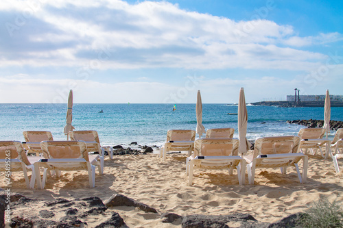 Poster Algérie Plastic lounge chairs and folded umbrellas on the shores of the Atlantic Ocean. North of Lanzarote. Canary Islands. Spain