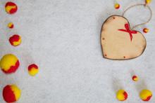 Wooden Heart And Fluffy Pom-poms On White Fleece Background