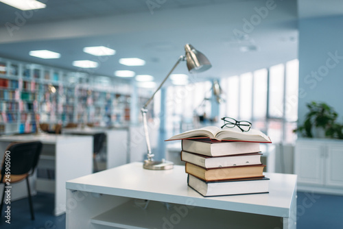 Fotografía  Stack of books and glasses on table in library