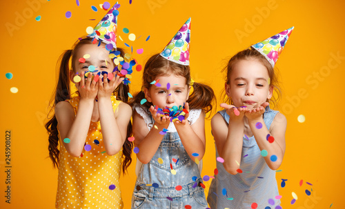 Photo  happy birthday children girls with confetti on yellow background