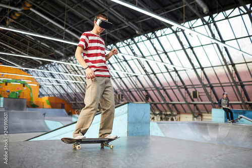 Young boy in casualwear standing on skateboard while training on parkour area or stadium and watching virtual adventure