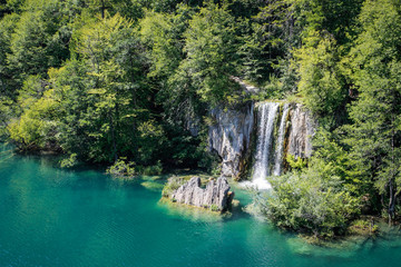 Fototapeta na wymiar The main natural landmark of Croatia is the Plitvice Lakes with cascades of waterfalls. Emerald clear cold water on the background of rocks, plants and trees.