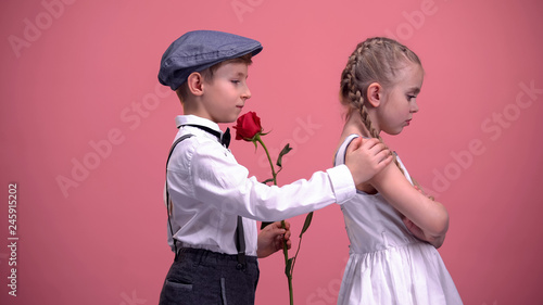 Little cute boy with red rose apologizing to offended girlfriend, first love Canvas Print
