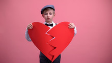 Sad Male Kid In Vintage Wear Trying To Fix Broken Paper Heart, Unrequited Love