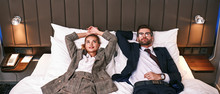 Two Tired Business People Laying On Bed In A Hotel Room