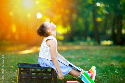 Happy adorable little kid girl reading book and holding
