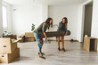 Lesbian couple carrying carpet in new home