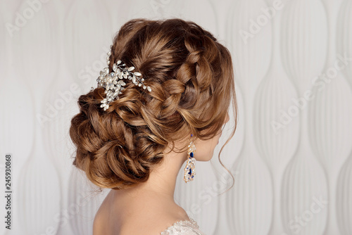 Wedding female hairstyle low beam on the head of a brown-haired girl back view on a light background.
