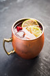 Sweet moscow mule with lime and raspberry in copper mug on the rustic background. Selective focus. Shallow depth of field.