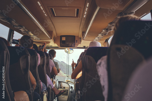 The tourist bus interior with people sitting
