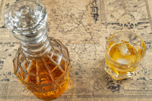 Whiskey Or Brandy Decanter With A Glass Of Whiskey On A Table, Covered In Old Parchment Paper Map.Soft Focus