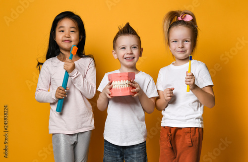fototapeta na drzwi i meble dental hygiene. happy little cute children with toothbrushes.