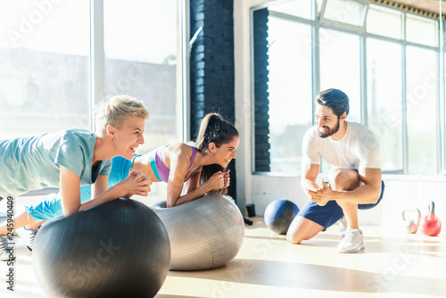 Leinwand Poster Two women smiling sporty women doing planks on pilates ball while their personal trainer kneeling and cheering for them