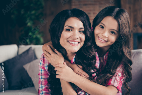 Close up photo two people cuddle mum little daughter satisfied adorable piggy back carry hold wear pink plaid shirts flat apartment room comfortable cozy couch sofa divan