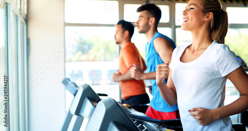 Poster Fitness Young attractive woman doing cardio training in gym