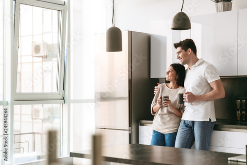 Fényképezés  Happy lovely young couple holding cups