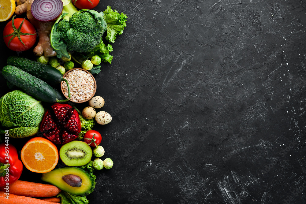 Fototapety, obrazy: Organic food on a black stone background. Vegetables and fruits. Top view. Free copy space.