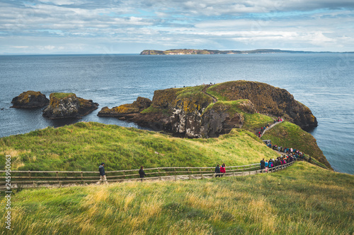 Tourists walking on the wooden path to the ocean. Northern Ireland. People hiking among the grass covered cliff to the Irish shoreline. Picturesque landscape. Ideal place for the outdoor activity.