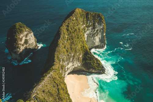Aerial shot of green covered cliff surrounded by the ocean. Nusa Penida island, Indonesia. Overwhelming marine scene. The steep shoreline next to the turquoise water surface.