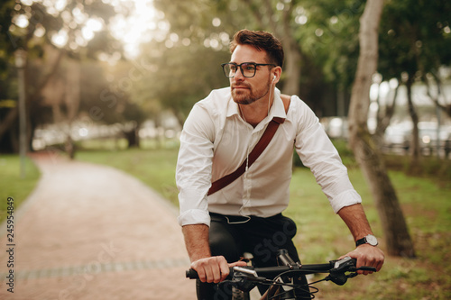 Businessman going to office on bicycle - 245954849