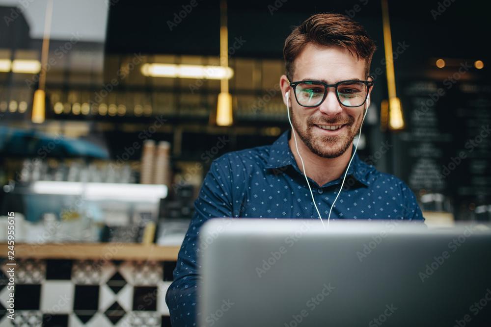 Fototapeta Man sitting in a restaurant using laptop