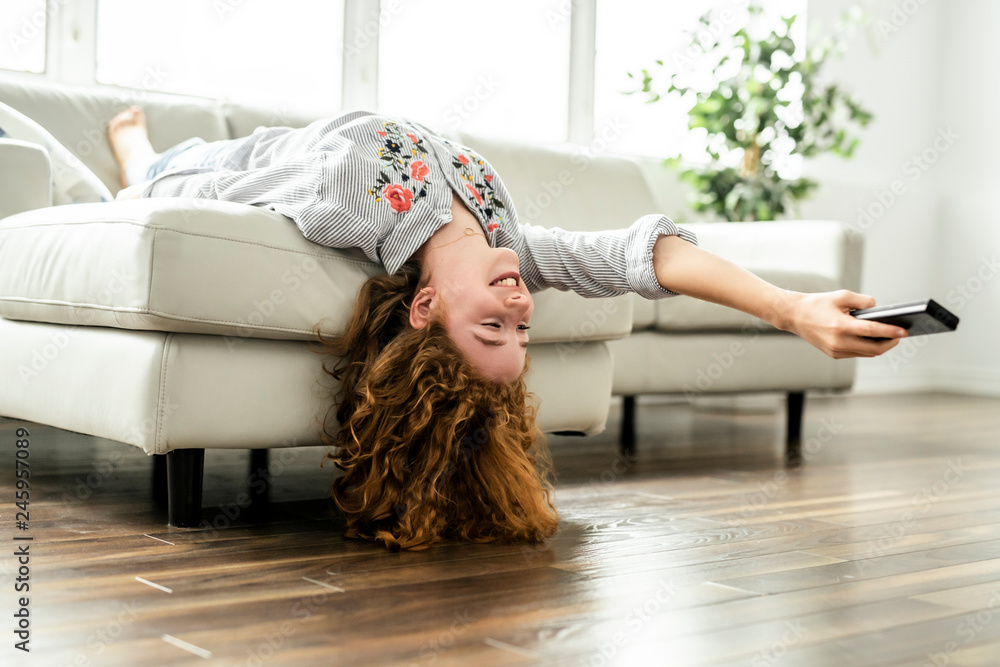 Fototapety, obrazy: Positive redhead teenage girl lying on a couch.