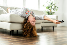 Positive Redhead Teenage Girl Lying On A Couch.
