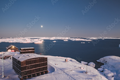 Photo sur Aluminium Antarctique Antarctic research Vernadsky station buildings next to the Antarctica shoreline. Stunning winter landscape. The snow covered land surrounded by the frozen ocean. The harsh environment. Night scene