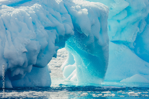 Foto auf Leinwand Blau Jeans Close-up arch of the iceberg. Antarctic landscape in the blue and white tints. Overwhelming scene of the ice covered glacier floating among the polar ocean. The geometric shapes of the ice mount.